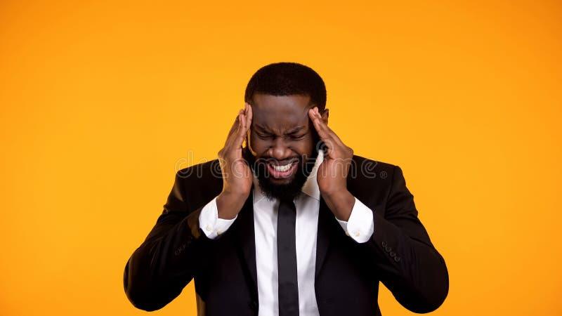 Dor de cabe?a de sofrimento masculina afro-americano cansado, viciado em trabalho antes do fim do prazo fotos de stock