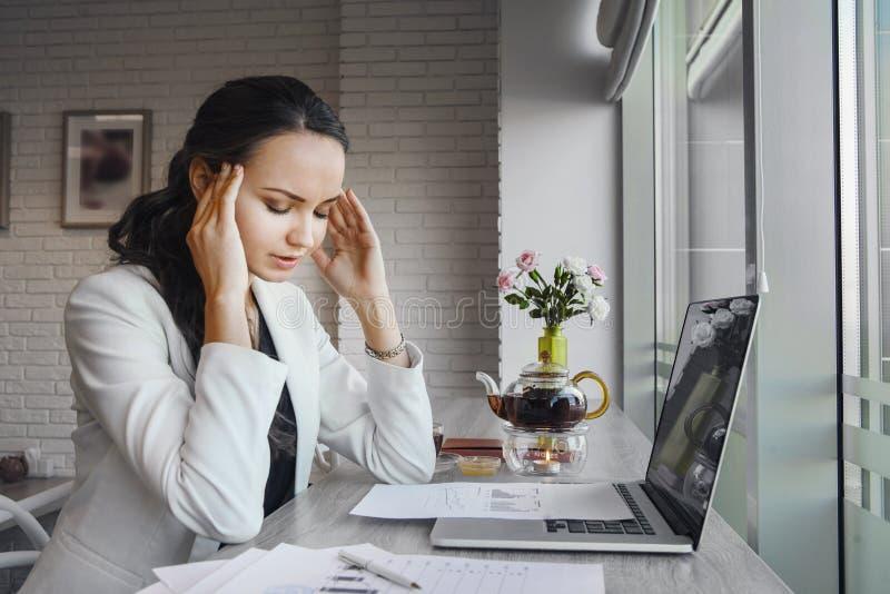A dor de cabeça terrível faz a mulher sofrer durante o dia de trabalho foto de stock