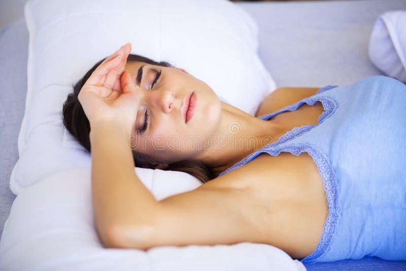 Dor de cabe?a Uma jovem mulher cansado, esgotada que sofra de uma dor de cabe?a severa da tens?o Retrato de um doente bonito foto de stock