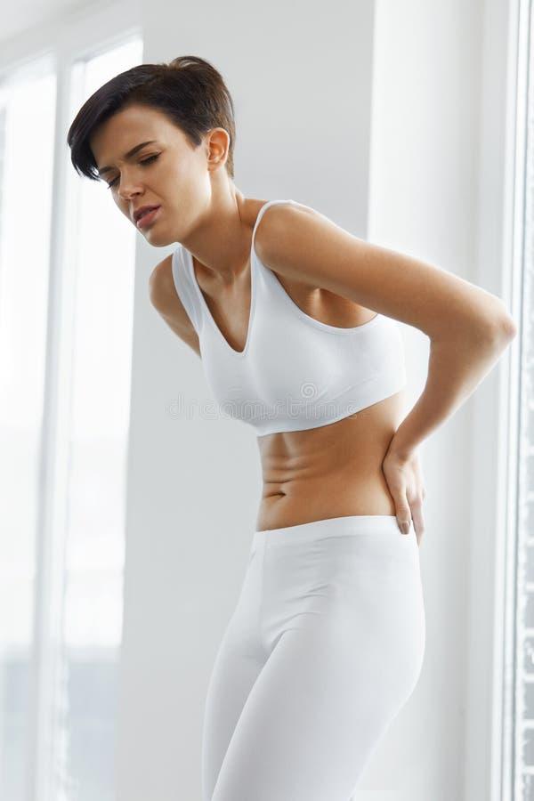Dor de corpo Da mulher do sentimento da dor parte traseira bonita dentro, dor lombar fotos de stock