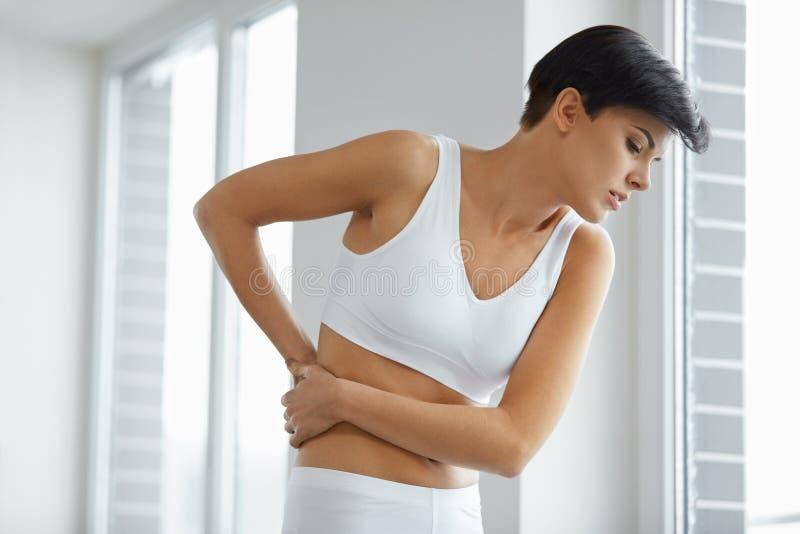 Dor de corpo Da mulher do sentimento da dor parte traseira bonita dentro, dor lombar imagens de stock