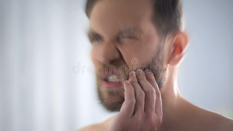 Dor de dente masculina nova do sentimento, mantendo a mão no mordente, problemas dentais, fim foto de stock