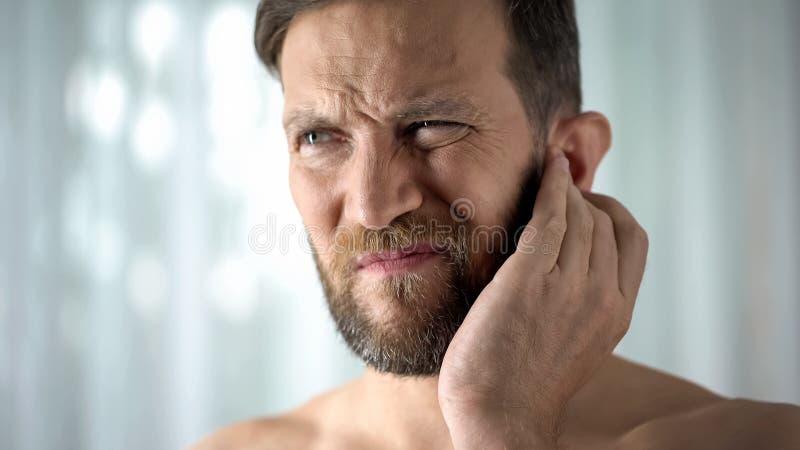 Dor de orelha doente do sentimento do indivíduo, cuidados médicos, infecção neurológica, otitis do itchiness imagens de stock