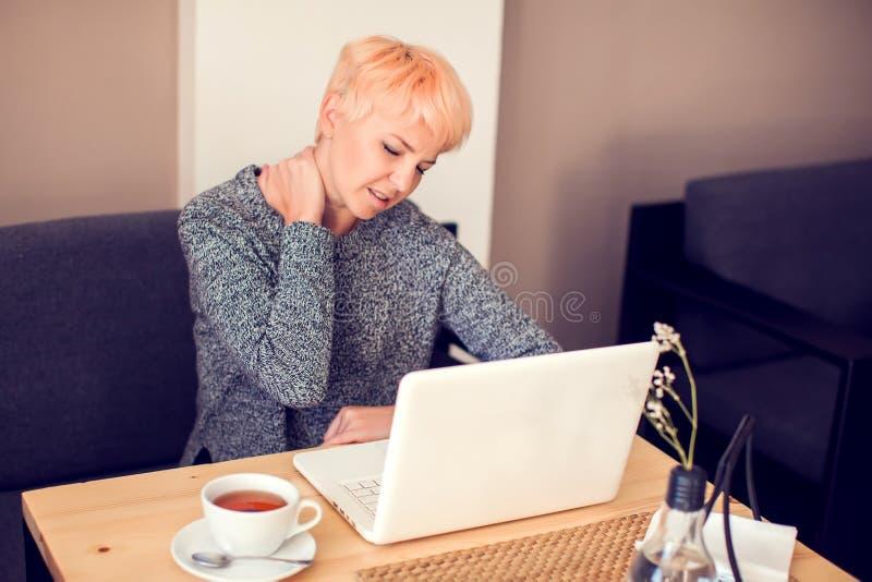 Dor de pescoço do sentimento da mulher ao trabalhar com portátil fotografia de stock