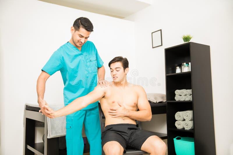 Dor de Suffering From Shoulder do atleta que submete-se à fisioterapia fotos de stock royalty free