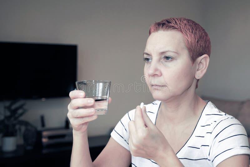 Dor desagrad?vel Mulher bonita infeliz triste que senta-se na tabela Depressão e dor de cabeça Toma um comprimido e lava-o para b imagens de stock