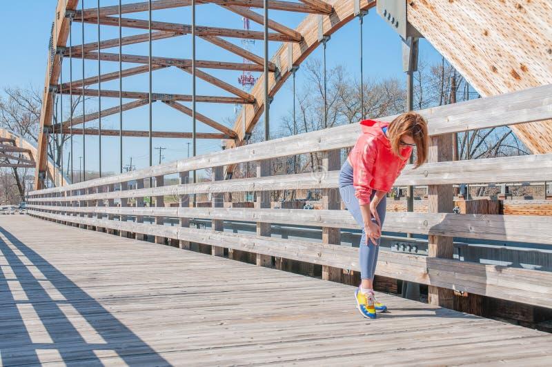 Dor do joelho Corredor fêmea com a lesão do músculo do esporte do pé imagens de stock
