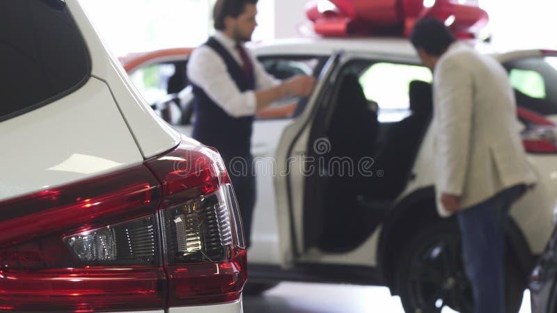 Dor för bil för bilåterförsäljareöppning för hans manliga kund arkivbild
