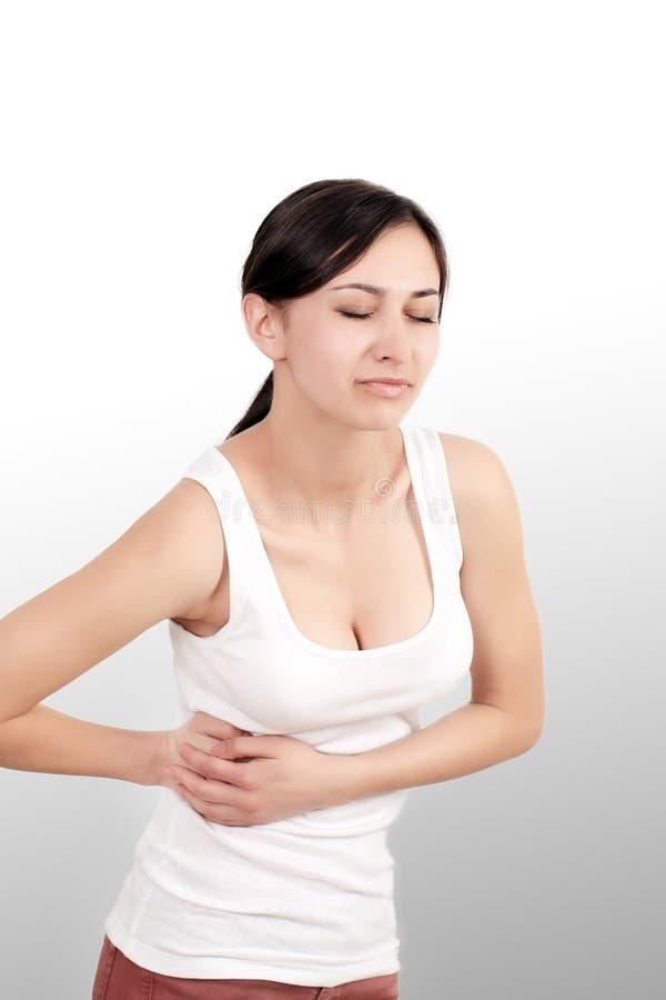 dor A mão da mulher que guarda abdominal com a dor de estômago que encontra-se em seja foto de stock
