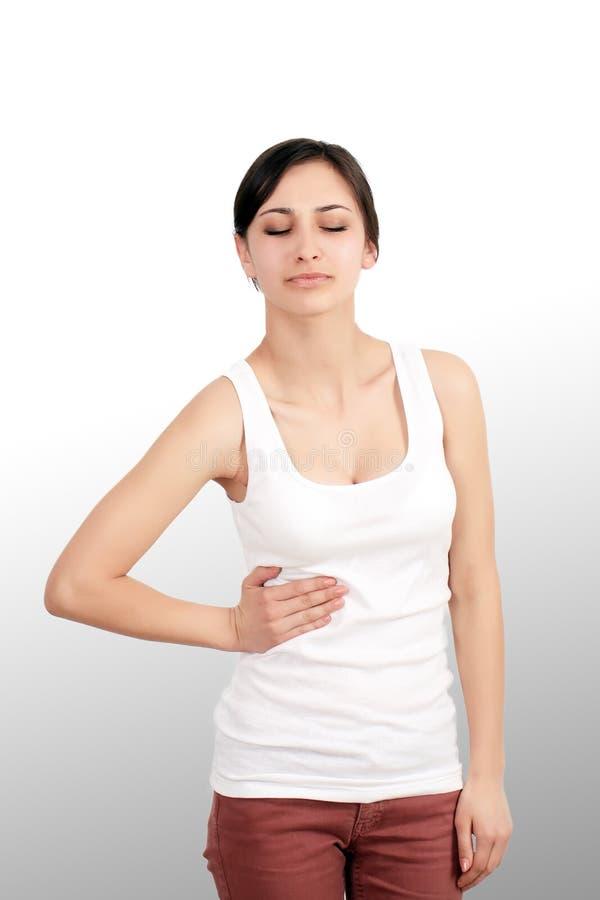 dor A mão da mulher que guarda abdominal com a dor de estômago que encontra-se em seja imagens de stock royalty free