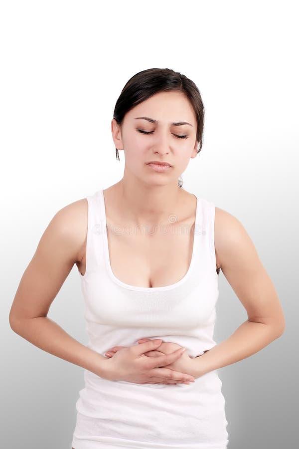 dor A mão da mulher que guarda abdominal com a dor de estômago que encontra-se em seja foto de stock royalty free