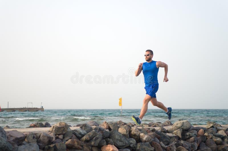 A dor não é nada comparado ao que sente como para parar Homem running na praia Ar livre de forma??o do corredor Esporte masculino fotografia de stock royalty free