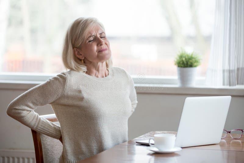 Dor nas costas de assento do sentimento da mulher madura virada que faz massagens a MU de dor imagens de stock