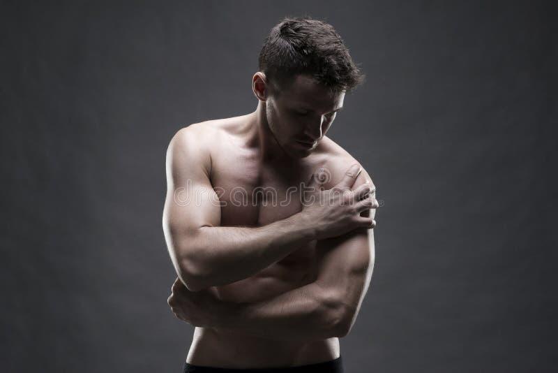 Dor no ombro Corpo masculino muscular Halterofilista considerável que levanta no fundo cinzento Baixo fim da chave acima do tiro  imagem de stock