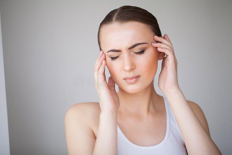dor O retrato de uma jovem mulher tem uma dor de cabeça foto de stock royalty free