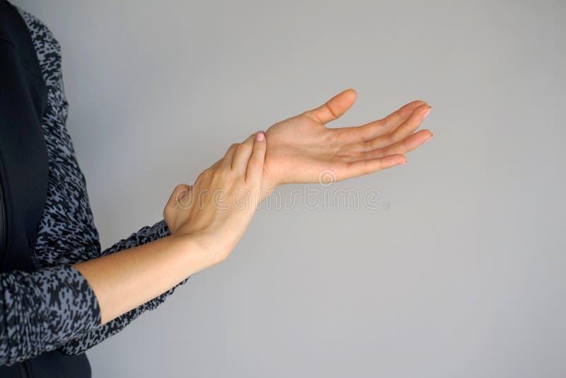 Dor severa em uma mão do ` s da mulher fotografia de stock