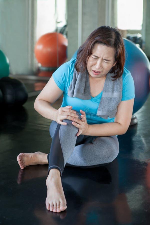 Dor superior do joelho de ferimento da mulher da aptidão ao exercitar no gym senhora envelhecida que sofre da artrite Exerc?cio f imagem de stock