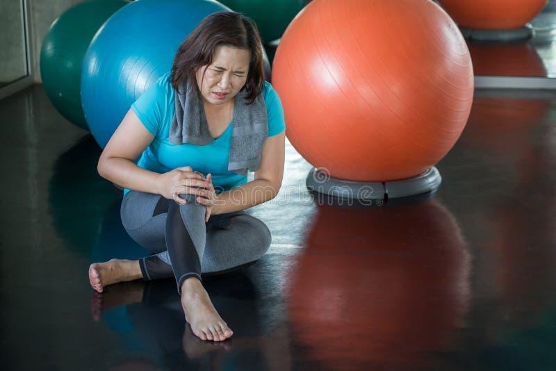 Dor superior do joelho de ferimento da mulher da aptidão ao exercitar no gym senhora envelhecida que sofre da artrite Exerc?cio f fotos de stock