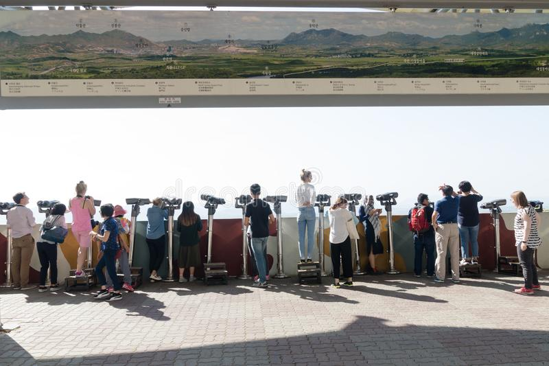 Dora Observatory, DMZ, South Korea - September 8 2017: Tourists watching with binoculars to North Korean village Propaganda villag. E or Peace village at Korean stock photography