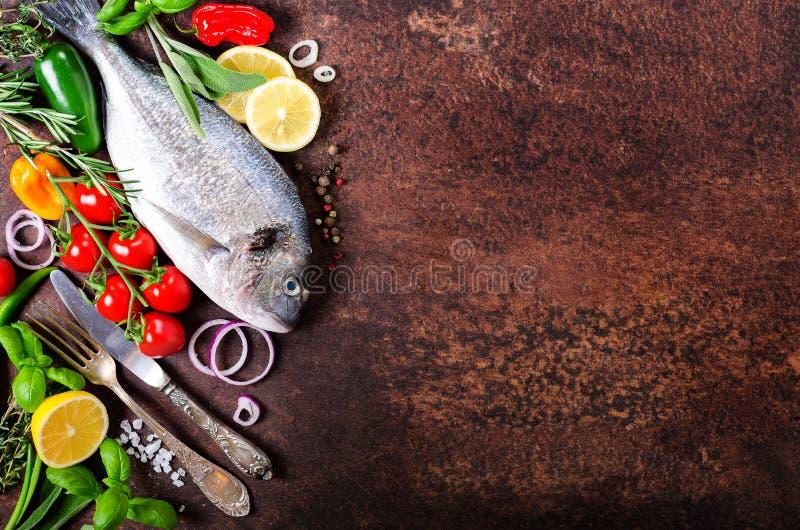Dorada, świeża ryba z warzywem, cytryna, ziele, cebula, papryka, czereśniowi pomidory, cebula, salton rocznika ciemny tło Odbitko zdjęcia royalty free