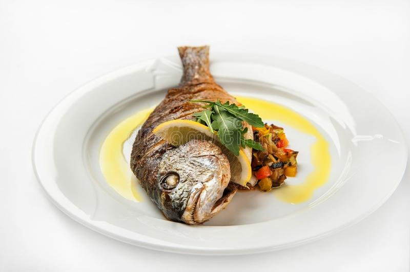 Dorada fish head close up. Grilled dorade on a white plate with sauce, arugula on a white plate isolated on whitebackground. Grilled dorade on a white plate with stock image