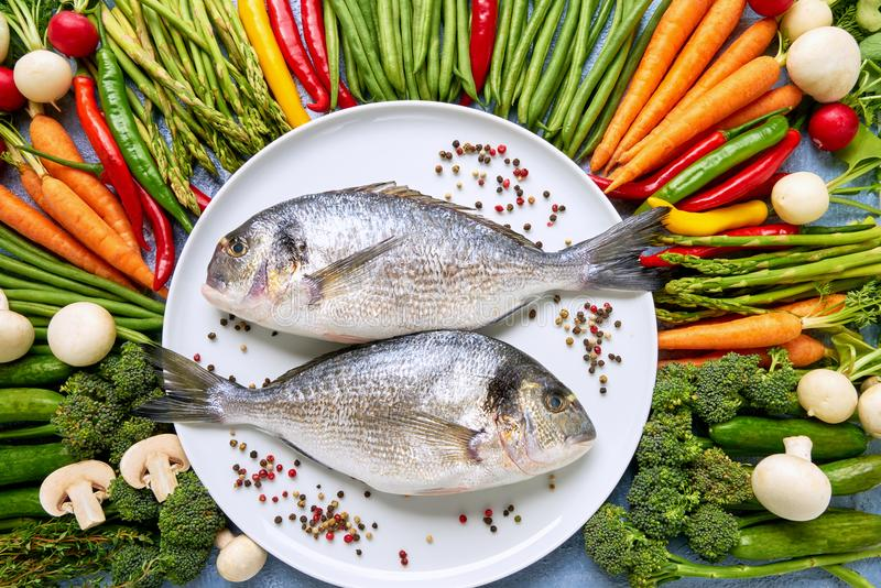 Dorada fish on white dish with colorful vegetables around. Dorada, carrots, tomatoes, asparagus, broccoli, chilli pepper, green b royalty free stock image