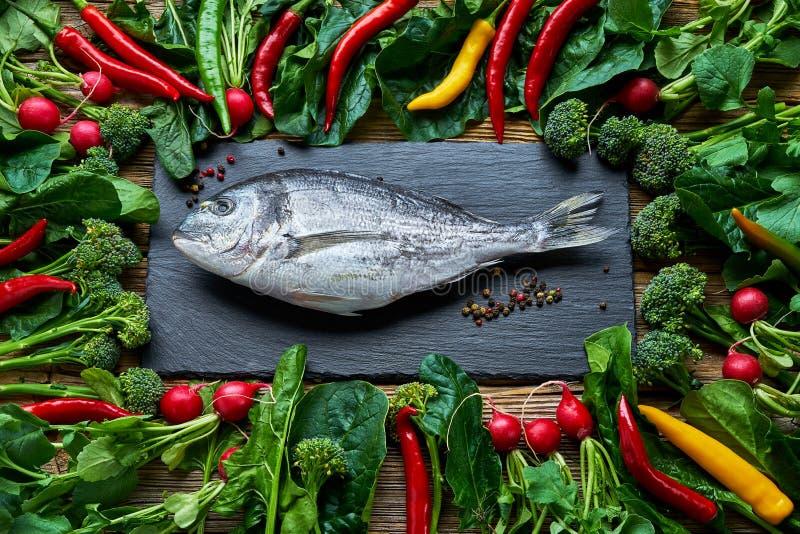 Doradavissen en groene groenten rond op oude houten lijst bovenkant stock foto's