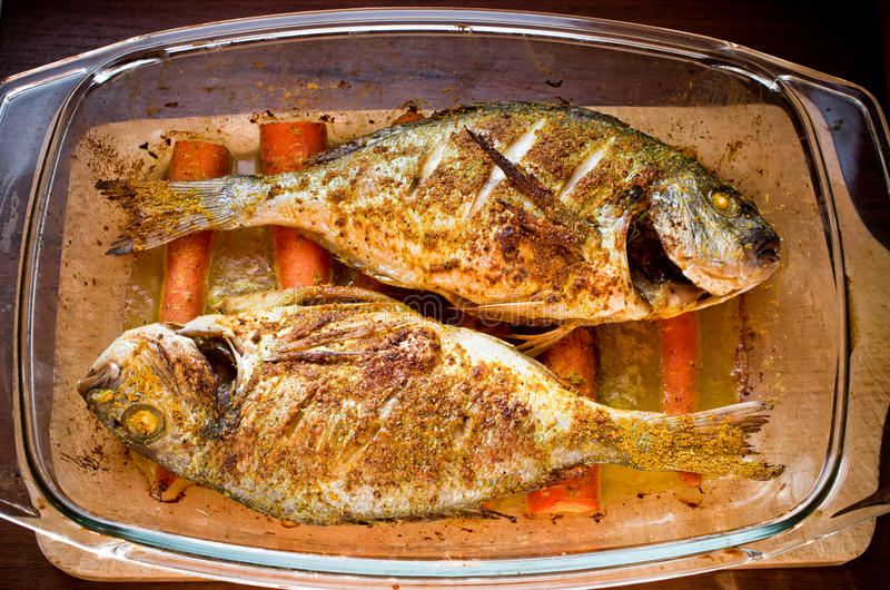 Dorade with curry on carrots in oriental style. Dorade baked with curry on the carrots in oriental style stock images