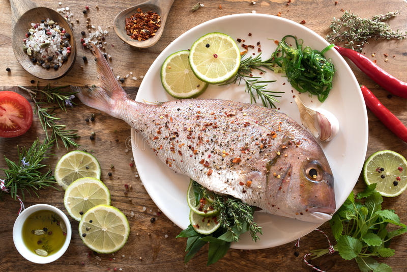 Dorade with herbs filling. Dorade fish with herb filling and ingredients for grilling stock photography