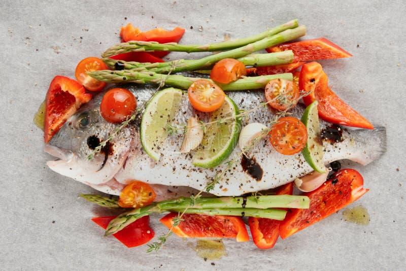 Dorade med grönsaker som är förberedda för stekande royaltyfria bilder