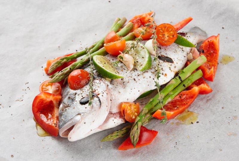 Dorade met groenten op het roosteren worden voorbereid die royalty-vrije stock afbeelding