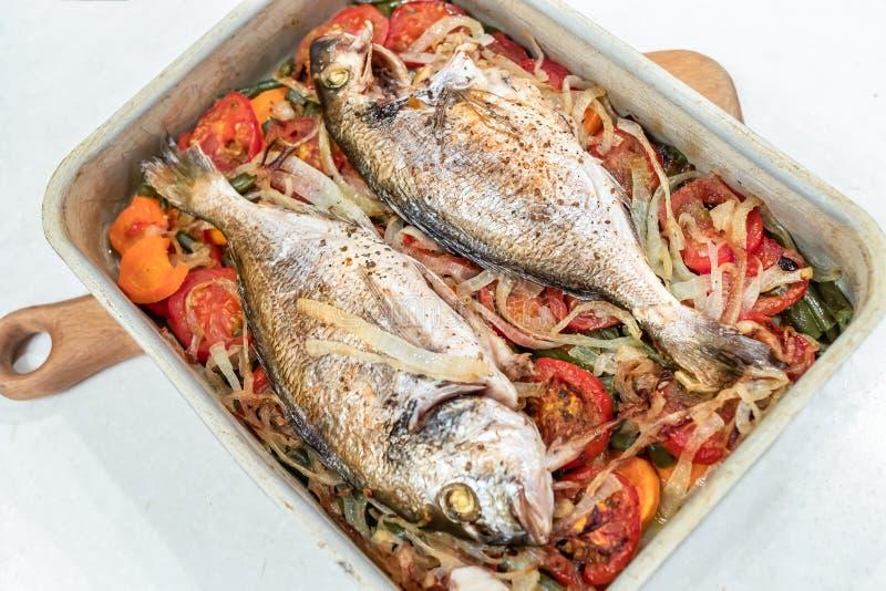 Dorado鱼,烹调在金属在白色背景的烘烤盘子菜坐垫  免版税库存图片