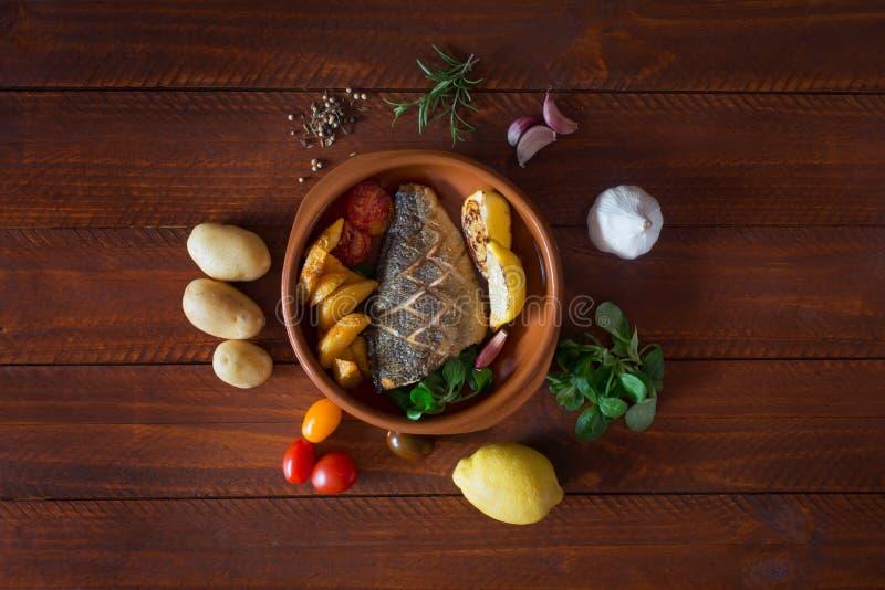 Dorado al forno con insalata e le verdure fresche Vista superiore Tavola di legno di Brown fotografia stock