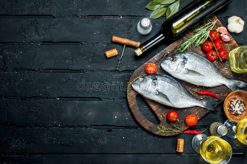Dorado cru dos peixes de mar com ervas, especiarias e uma garrafa do vinho branco imagens de stock royalty free