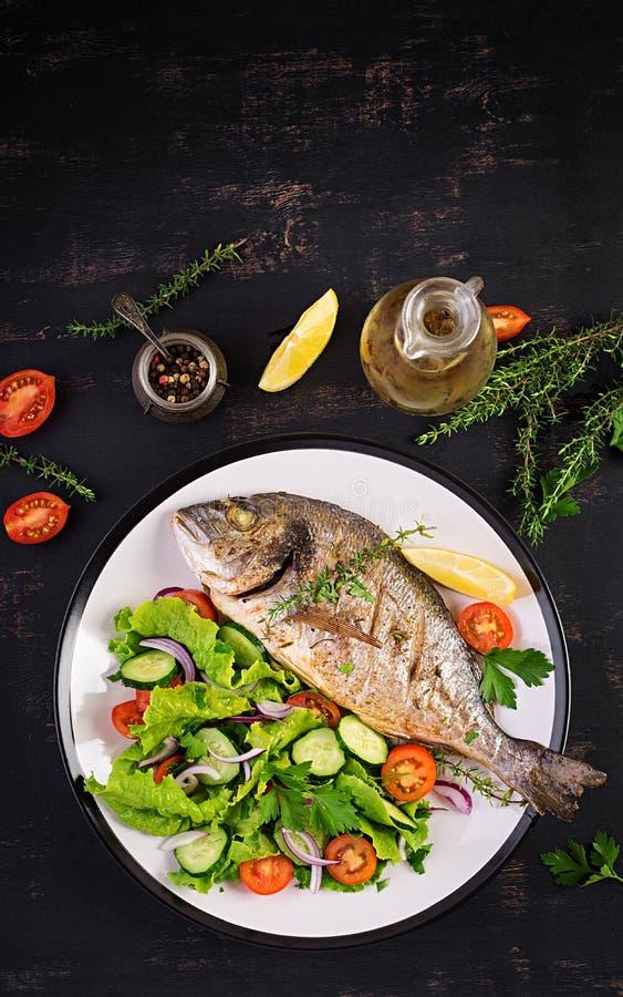 Dorado cuit au four de poissons avec le citron et la salade fraîche dans le plat blanc sur le fond rustique foncé photo libre de droits