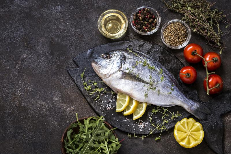 Dorado fish with fresh vegetables and herbs. On a dark background royalty free stock photo