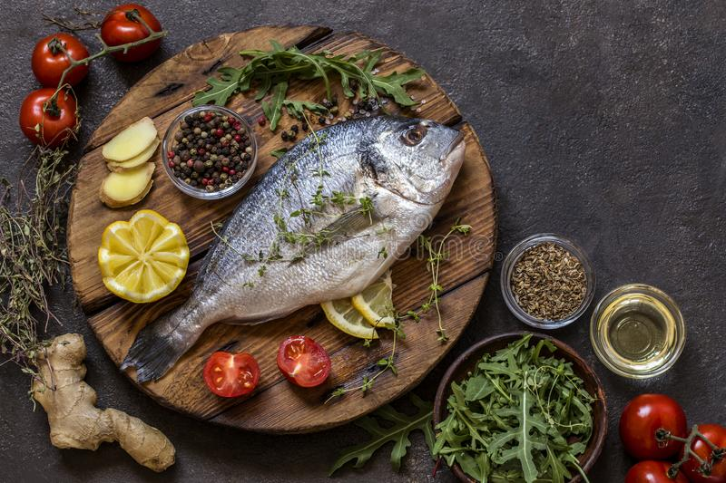 Dorado fish with fresh vegetables and herbs. On a dark background royalty free stock photos