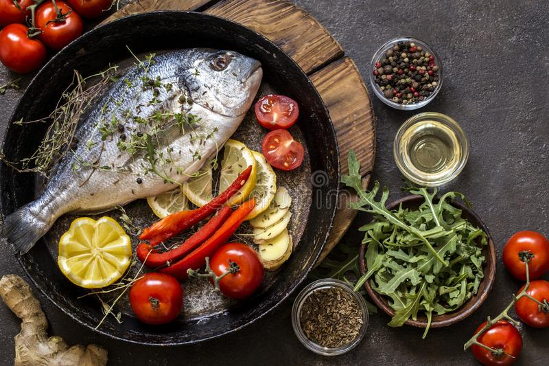 Dorado fish with fresh vegetables and herbs. On a dark background stock photography