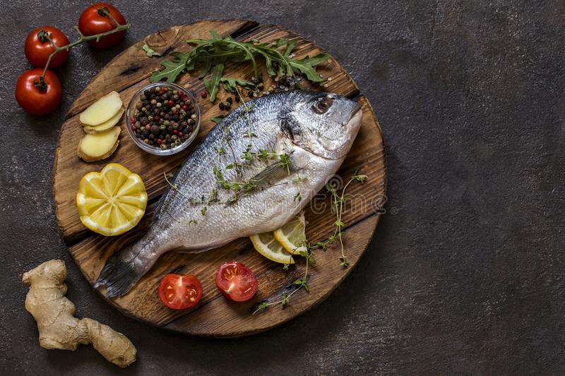 Dorado fish with fresh vegetables and herbs. On a dark background stock image