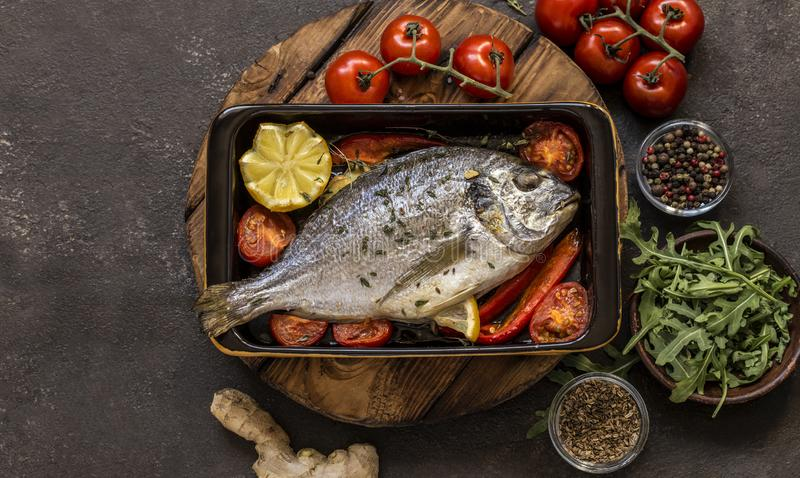 Dorado fish with fresh vegetables and herbs. On a dark background royalty free stock photography