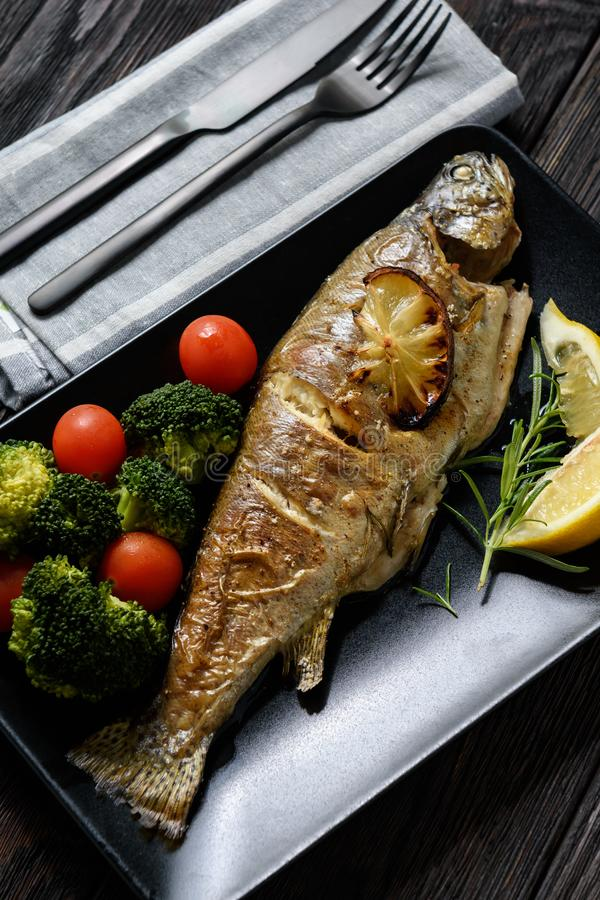 Dorado fish, roasted in oven, with tomatoes and broccoli. royalty free stock image