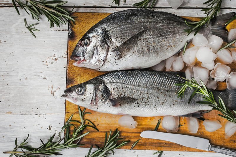 Dorado fish and sea bass with rosemary. On the wooden board stock photos