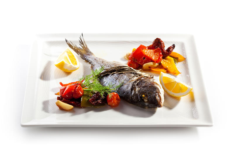 Dorado. Fried Fish (Dorado). Garnished with Lemon and Vegetables stock image
