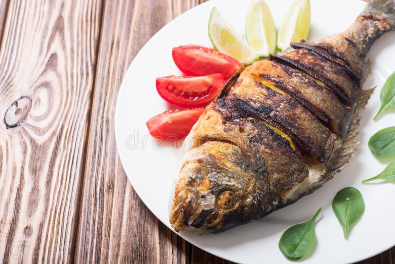 Dorado frito de los pescados con la cal, los tomates y la espinaca imagenes de archivo