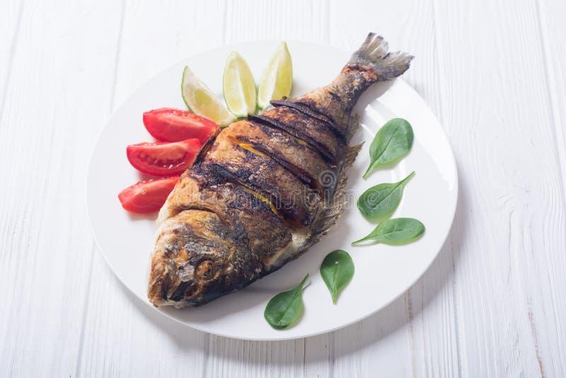 Dorado frito de los pescados con la cal, los tomates y la espinaca imagen de archivo libre de regalías