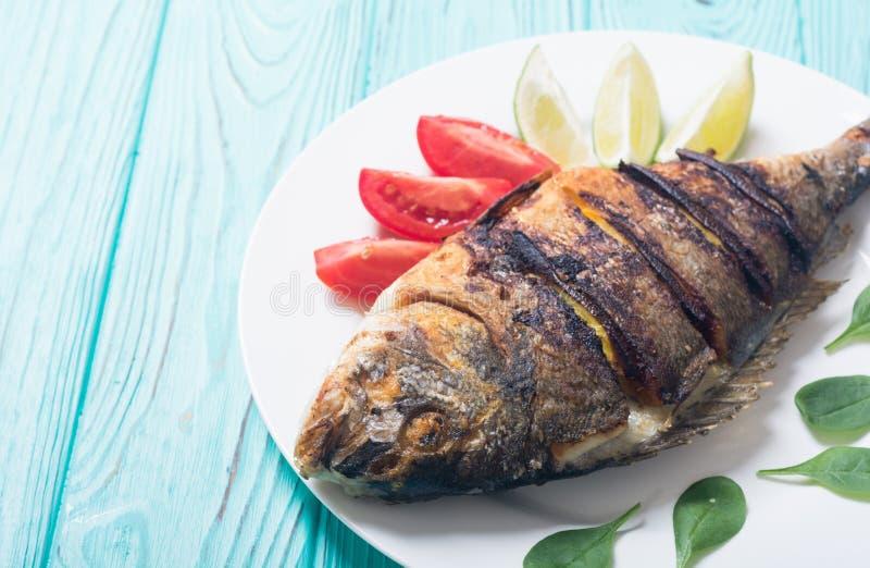 Dorado frito de los pescados con la cal, los tomates y la espinaca fotografía de archivo libre de regalías
