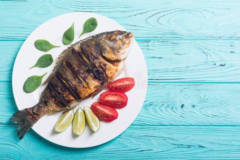 Dorado frito de los pescados con la cal, los tomates y la espinaca imágenes de archivo libres de regalías