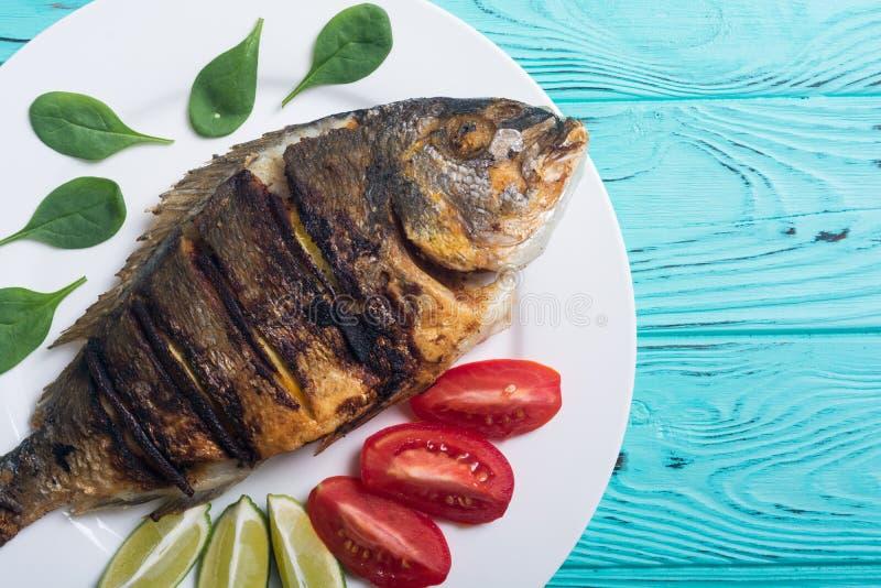 Dorado frito de los pescados con la cal, los tomates y la espinaca Alimento de mar foto de archivo