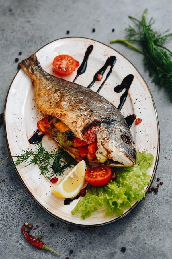 Dorado grillade stoppat med grönsaker på en vit platta på en grå bakgrund royaltyfri foto