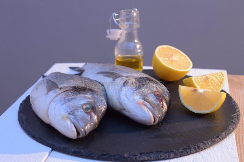 Dorado ryba na czarnym talerzu z cytryną zdjęcie stock